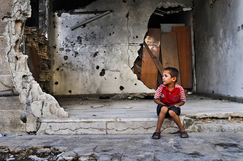 Boy sitting in front of a destroyed house in Homs, Syria.