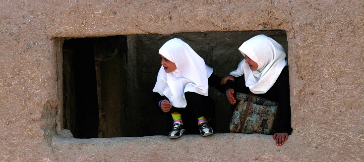 Two school girls peer out of a window in Herat, Afghanistan.
