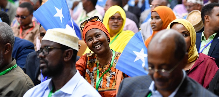 Women laughs at the camera during a meeting of senior officials of the Federal Government of Somalia and Federal Member States, UN representatives and members of civil society organizations at the closing session of the national constitutional convention in Mogadishu on 15 May 2018.