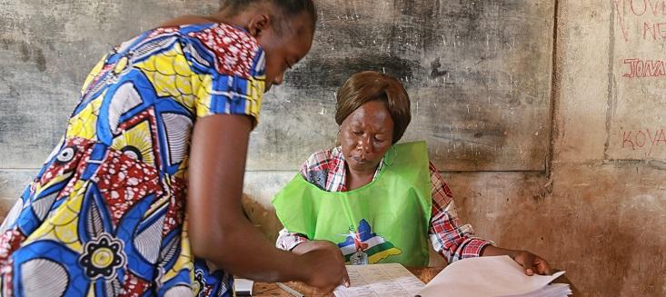Une personne responsable des élections (à droite) assiste une électrice dans un bureau de vote lors du second tour de l'élection présidentielle en République centrafricaine.