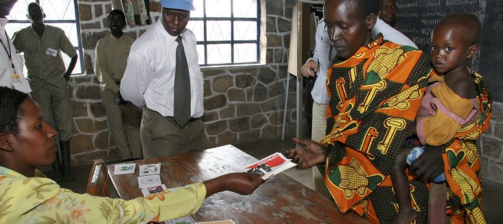 Under the eyes of international observers a woman gets her voter's cards for the election of communal councillors in Cancuzo in Burundi. June 2005